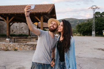 Couple of a boy and a young woman taking a selfie and smiling wi