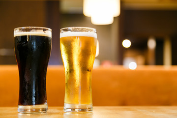 Two glasses of fresh cold beer. A glass  dark , the other light.