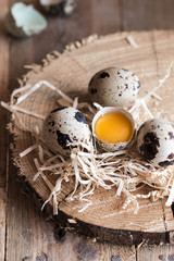 Quail raw eggs in a wooden tray and rustic table