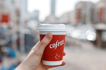Hand holding a red cup of coffee on the background of the city.