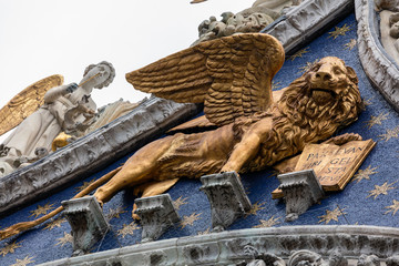 The winged golden lion of St Mark on the facade of the San Marco Basilica in Venice, Italy
