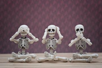 Three skeletons pose as three wise monkeys Fotoväggar
