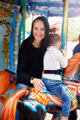 Mom and daughter in the park and ride on the carousel