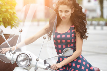 Young beautiful italian woman sitting on a vintage scooter