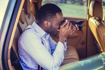 A black man using dslr camera in a car.