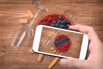 Hands taking photo wine glass with berries  with smartphone.