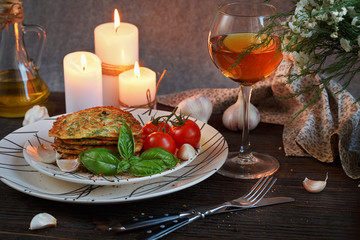 Vegetarian zucchini fritters served with fresh herbs, tomatoes a