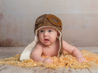 lovely little baby in pilot hat crawling on wooden floor