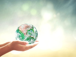 World environment day concept: Earth globe in human hands over blurred nature background.. Elements of this image furnished by NASA