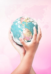 World environment day concept: Earth globe in two human hands over blurred pink nature background. Elements of this image furnished by NASA