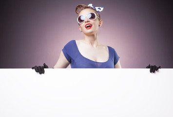 Smiling Pin Up girl holding a white board