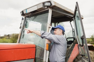 Farmer pointing by tractor