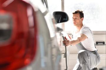 Mechaniker repariert Unfallschaden vom Auto in einer Werkstatt // car repair