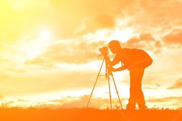 Silhouette man photographer on sunset