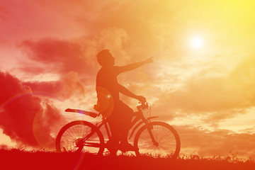Silhouette  man with bicycle at sunset. relax time