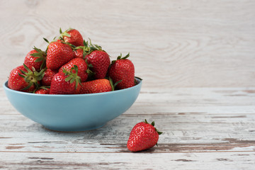 Pile of juicy ripe organic fresh strawberries in a large blue bowl. Light rustic wooden background.