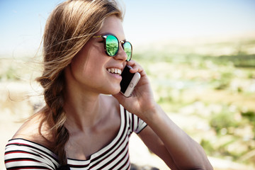 Young smiling female talking on cell phone outside on the nature on a sunny day. Concept of mobility and communication.