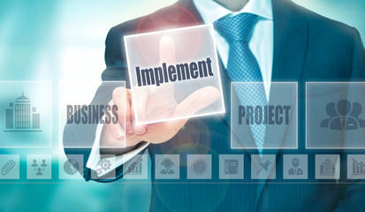A businessman selecting a Implement Concept button on a clear screen.