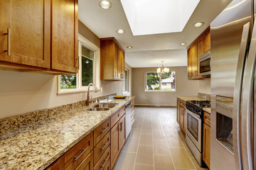 Modern kitchen room with matte brown cabinets, shiny granite tops