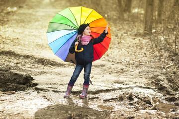 Girl with multicolored umbrella in autumn park