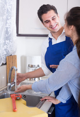 Satisfied housewife and repairman standing near sink