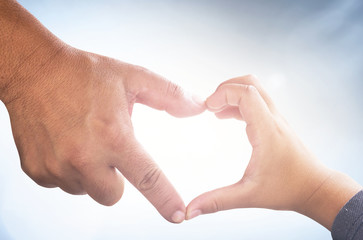 International human solidarity day concept: Father's and son's hands forming shape of heart on blurred sunshine blue sky background