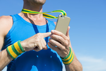 Brazilian athlete with green and yellow Brazil color wristbands using gold medal mobile phone against blue sky