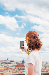 Young girl taking a picture of Prague city
