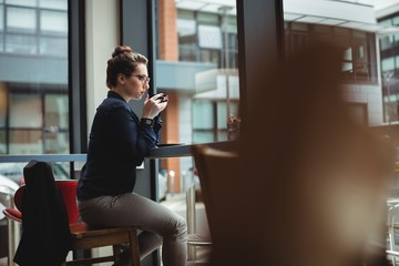 Woman drinking coffee while sitting on chair