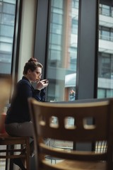 Thoughtful woman drinking coffee in cafe