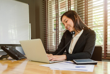woman working in office and talking telephone and smiling