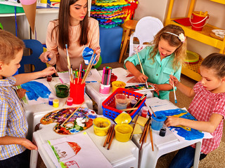 Children painting on paper at table in primary school. Teacher woman learn children paint.
