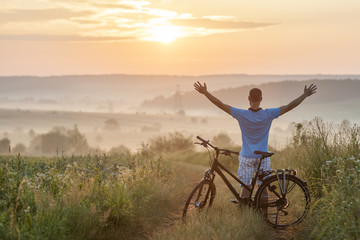 Young man standing near  bicycle in morning sunrise with wonderf