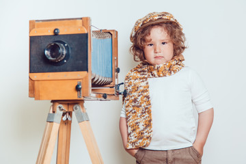 Little boy standing near the camera on a white background