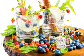 refreshing summer drinks detox water in glass with wild strawberry,blueberry,rhubarb,ice and mint on a white background.
