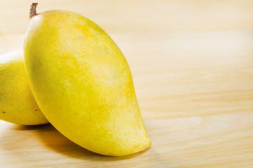 mangoes, yellow mangoes isolated on wood table background.
