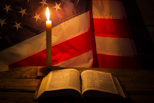 Burning candle and open book. America's flag behind burning candle. Night at old church. Never lose faith.