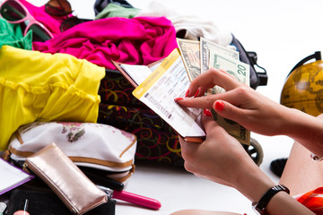 Hands holding dollars and ticket. Lady' hands near clothes pile. Boat ticket and US dollars. It's time to pack things.