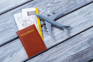 Passport near toy plane. Tickets and a document. Ticket to another country. Vacation time has finally come.