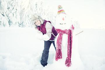 Seniorin im Schnee mit Schneemann