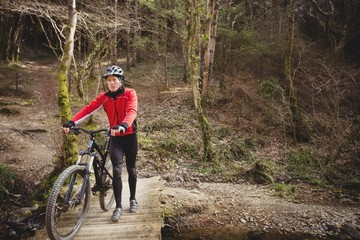 Mountain biker walking with bicycle on footbridge