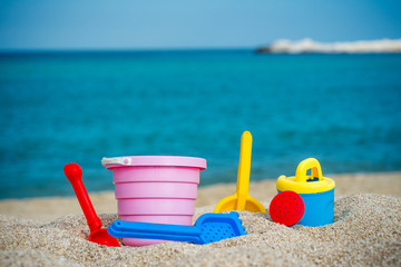 Children's beach toys - buckets, spade and shovel on sand on sunny day