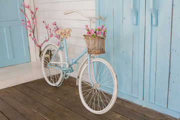 Papiers peints Velo white and blue vintage bicycle with flowers in a basket