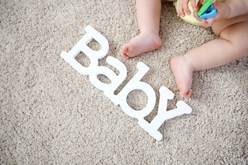 Baby legs and decorative word on the floor