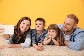 Happy family taking selfie on yellow wall background