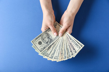 Woman hands holding money on blue background