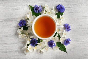 Cup of tea with fresh flowers lying around on wooden background