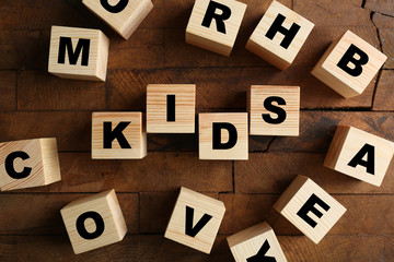 Word KIDS on wooden background