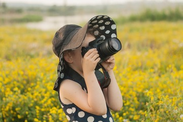 Young girl, reflex camera and field. A summer background