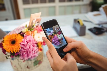Hands of female florist taking photograph of flowers